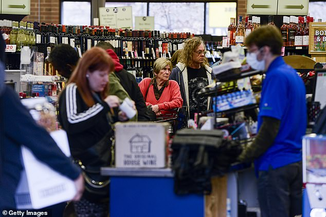 A cashier wore a mask to protect himself as a frenzy of Denver customers stocked up on wine and beer on Monday at Argonaut Wine and Liquor