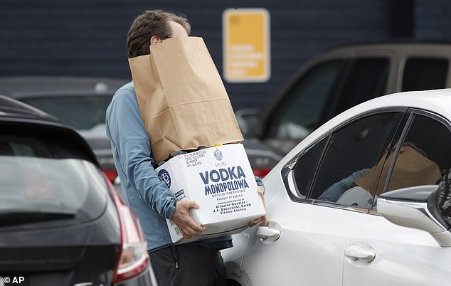 Ready to bunker down: This shopper struggled to open his car door while juggling purchases from the liquor store
