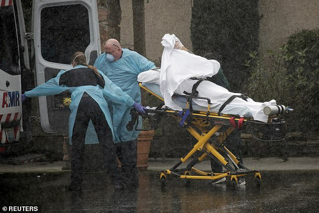 She said redness around the eyea was the most important sign that someone was infected with the virus. Pictured:Medics transport a patient through heavy rain into an ambulance at the Life Care Center, March 7