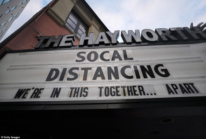 A movie theater sign in Los Angeles urges the public to practice social distancing