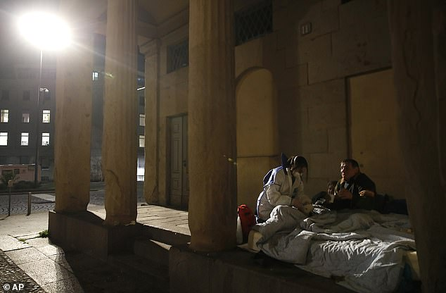 A volunteer nurse wearing a mask tends to a homeless person in Milan last night. Thousands of health workers have themselves been infected with coronavirus