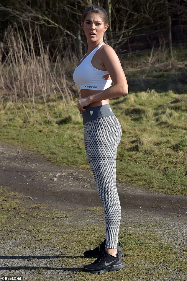 Wow: Rebecca looked sensational as she showcased her toned curves in a tiny white crop top and grey patterned gym leggings