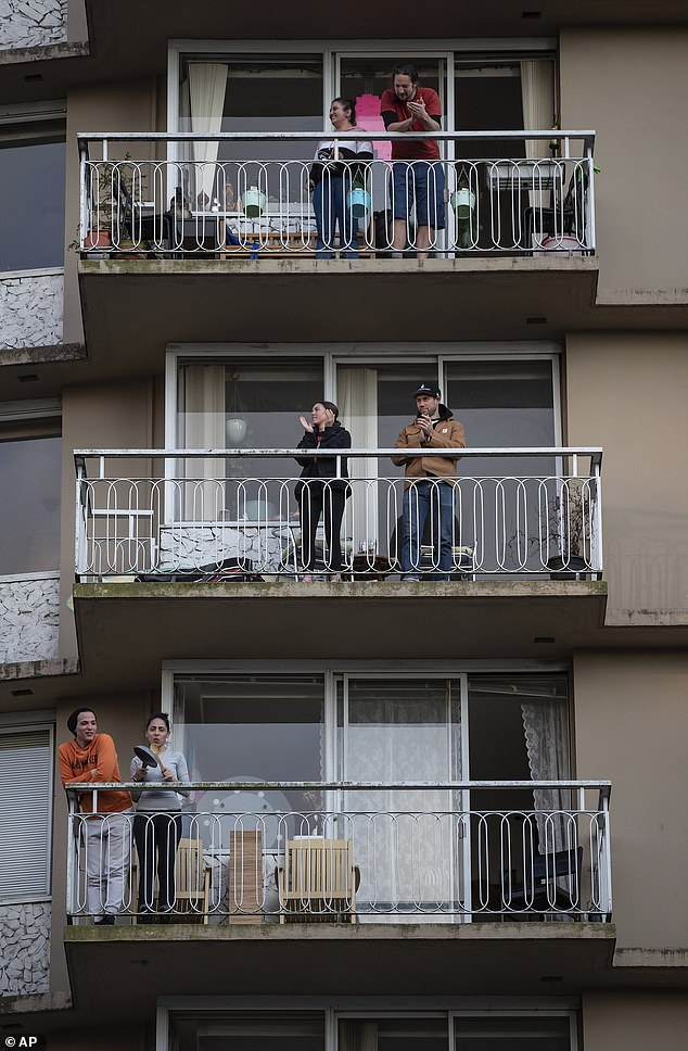 Residents on apartment balconies in Vancouver are pictured Tuesday applauding and making noise in a daily show of support for healthcare workers who helping fight the coronavirus