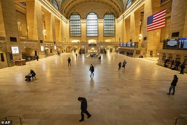 Люди пробираются в почти пустой Большой Центральный Терминал, в среду на Манхэттене