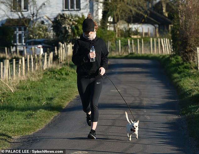 Covered up: Summer's auburn tresses were hidden beneath her cap as she enjoyed a run with her adorable dog