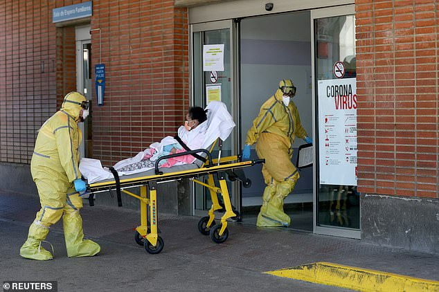 Ambulance workers in full protective gear arrive with a patient at the Severo Ochoa Hospital during Spain's coronavirus outbreak