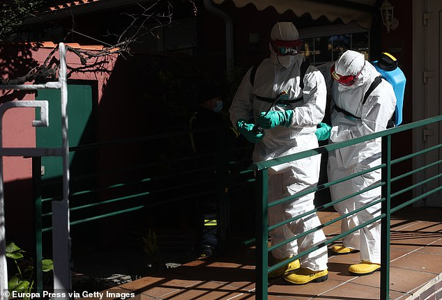 Members of the military suit up as they prepare to disinfect a nursing home in Madrid today