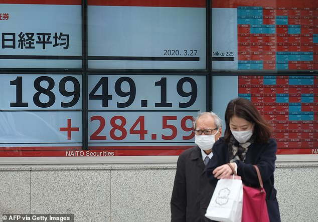 Pedestrians wearing face masks pass a board for the Tokyo Stock Exchange in Tokyo today