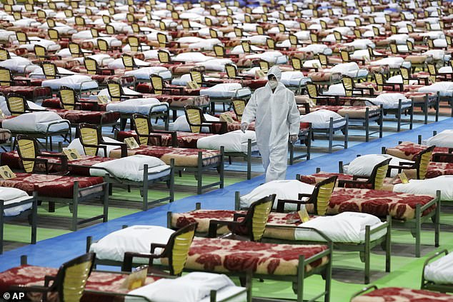 A person in protective clothing walks through a temporary 2,000-bed hospital set up by the Iranian army at the international exhibition center in northern Tehran, Iran, on Thursday