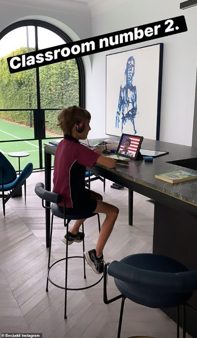 Temporary classroom: Rebecca documented the homeschooling sessions, with eldest son Oscar, eight, taking an online class on his iPad while sitting at a marble table overlooking the tennis court