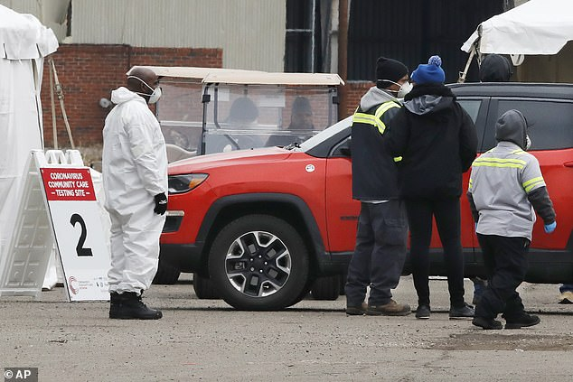 Health care officials watch as a vehicle approaches a testing site at the Michigan State Fairgrounds in Detroit