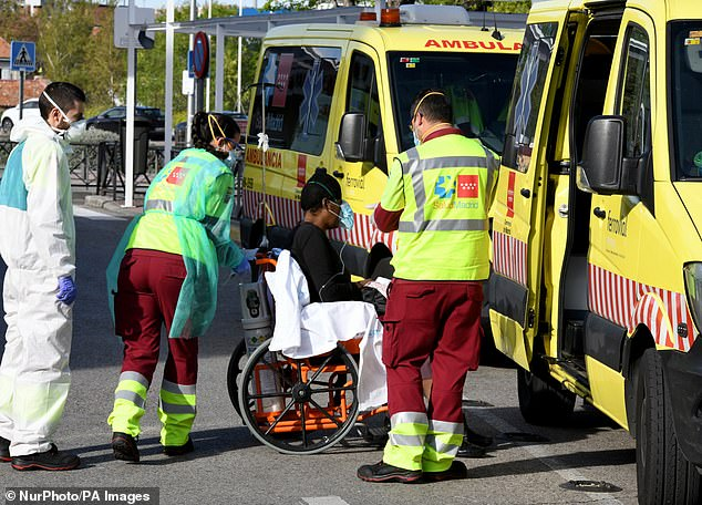 Spain is now the fourth worst effected country in the world. Pictured: Medical staff in Madrid transfer a patient in a wheelchair