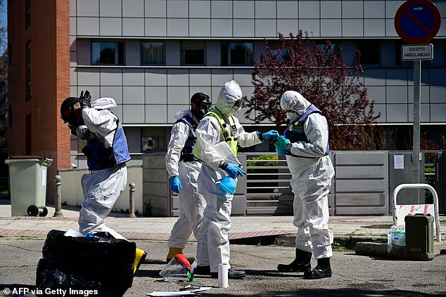 Spain has registered a record number of coronavirus deaths in a single-day period. Pictured:Members of the Military Emergencies Unit (UME) prepare to carry out a general disinfection