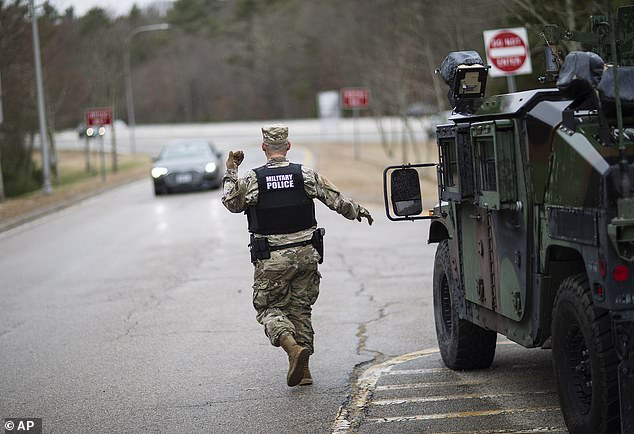A member of the Rhode Island National Guard Military Police directs a motorist with New York license plates at a checkpoint on I-95 near the border with Connecticut on Saturday. All New York motorists must register and self-quarantine