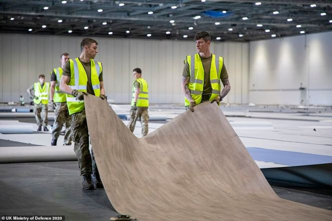 Soldiers help lay the flooring down as the new NHS Nightingale Hospital prepares for its first patients next week