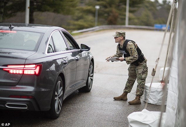 A member of the Rhode Island National Guard Military Police talks with a motorist with New York license plates at a checkpoint on I-95 near the border with Connecticut on Saturday