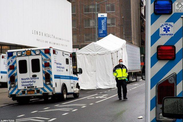A paramedic walks next to a makeshift morgue set outside Lenox Health Medical Pavilion on Sunday