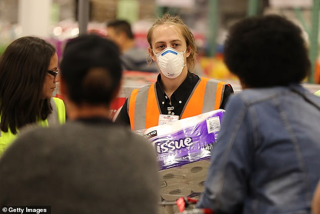 Staff members (pictured) in mask assists shoppers buying toilet paper at Costco Perth on March 19, 2020 in Australia
