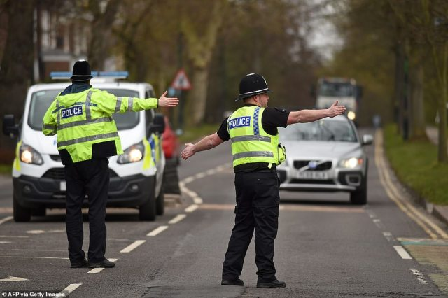 """Police officers from North Yorkshire Police stop motorists in cars to check that their travel is """"essential"""" in York today"""
