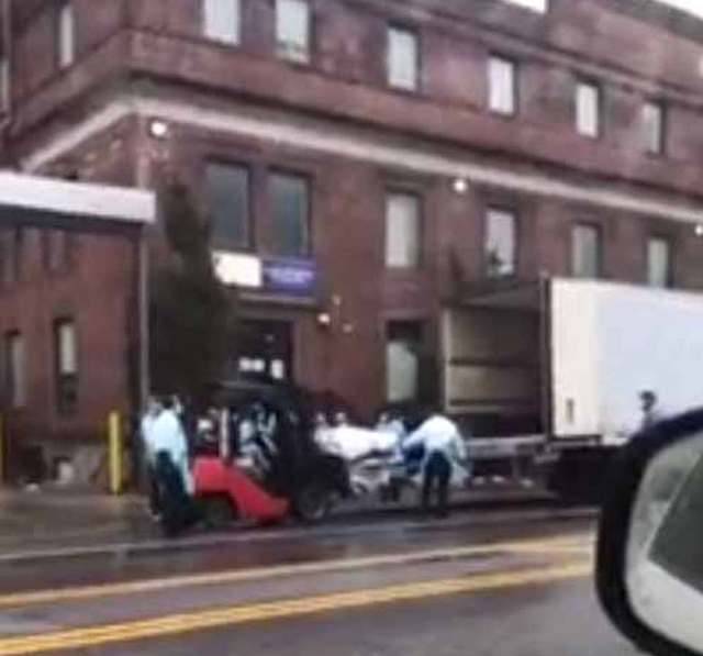 A pallet of bodies in loaded on to a refrigerated truck outside a hospital in Brooklyn yesterday as covid-19 grips the city of New York