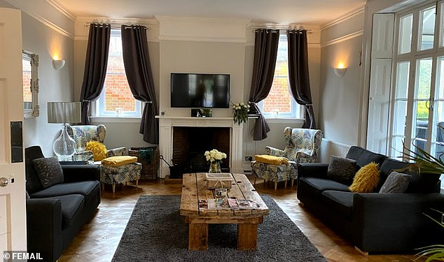 The interior design is impeccable throughout, with dark grey sofas broken up by bright yellow cushions and throws