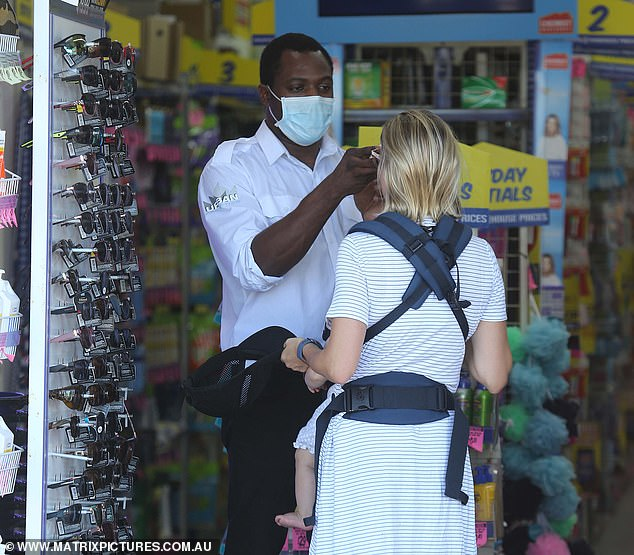 A mother is seen outside a Chemist Warehouse store in Sydney having her temperature checked on Tuesday (pictured)