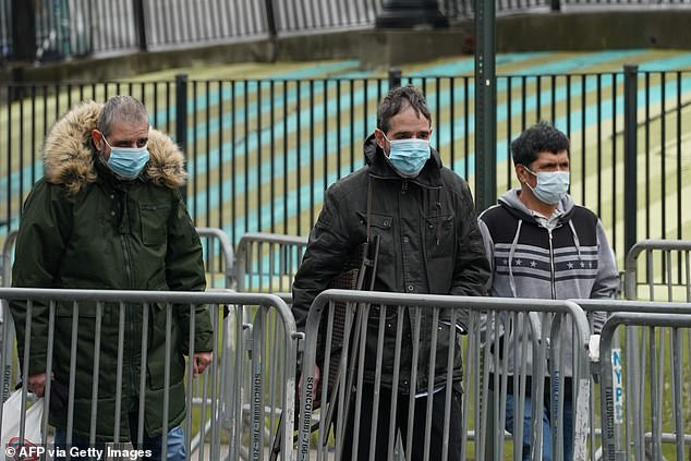 People wearing masks walk past Elmhurst Hospital in the Borough of Queens on March 31, 2020 in New York. Officials are considering changes in recommendations for ordinary Americans in the community