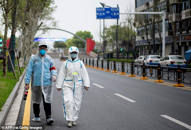 A couple wearing protective suits as a preventive measure against coronavirus walk along a street in Wuhan in China's central Hubei province
