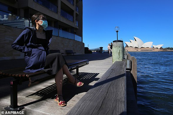 The coronavirus could become harder to battle as winter sets in (pictured, a woman wearing a mask in front of Sydney Opera House on March 13)