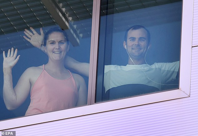 Returning overseas passengers Kate and Tim are seen through their hotel room window while in quarantine at the Novotel in Brisbane, Australia