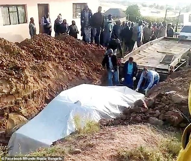 Villagersin Jozana village in Sterkspruit, watching the chief's Mercedes lowered into the 8ft-deep grave under a large white sheet with him inside holding the steering wheel