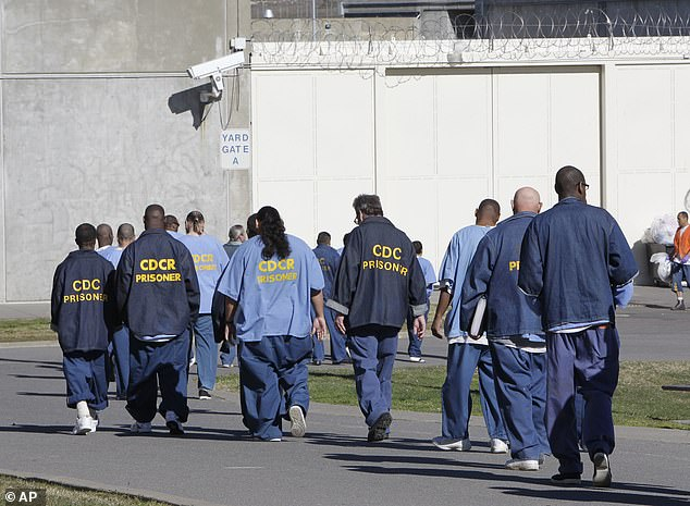 In this 26 February, 2013, file photo, inmates walk through the exercise yard at California State Prison Sacramento, near Folsom, Calif. From today, inmates will be locked down at US federal prisons to prevent the spread or infections of coronavirus