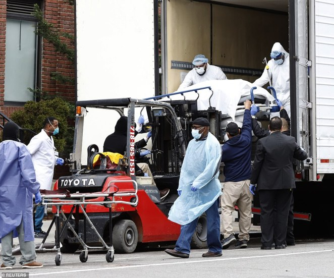 Pictured, dead bodies are loaded onto a truck outside Brooklyn Hospital Center inNew York on Tuesday