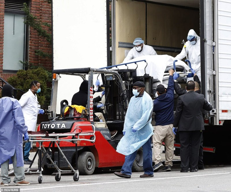 Pictured, dead bodies are loaded onto a truck outside Brooklyn Hospital Center in New York on Tuesday