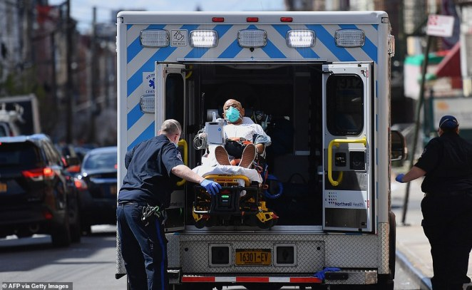 Paramedics transport a patient wearing a face mask to the emergency room entrance of the Wyckoff Heights Medical Center in Brooklyn. New York continues as the epicenter of the outbreak but there are concerns Detroit will be a new hot spot