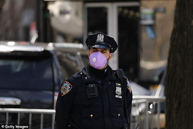 A police officer stands outside Mount Sinai Hospital on April 1. NYPD forced to beg government to send more masks for officers after cops risked their lives by responding to house calls without protective gear