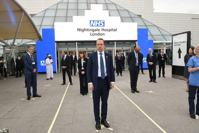 Health Secretary Matt Hancock, pictured at the opening of Nightingale Hospital in London today, suggested that the UK lockdown would be in place until the end of April at the earliest
