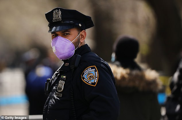 On Thursday,the NYPD revealed that coronavirus cases continued to surge among their employees, with more than 1,500 now testing positive to the disease. An NYPD officer is pictured on duty Wednesday