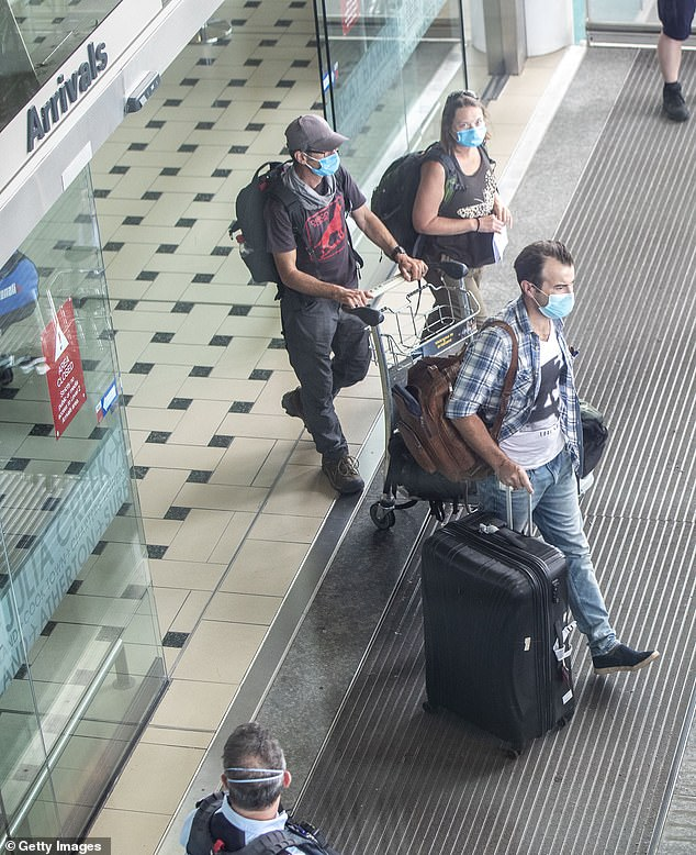 Passengers and police are seen wearing face masks after arriving at Brisbane International Airport