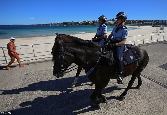 Police on horses enforce social distancing regulations to slow the spread of the coronavirus at Bondi Beach on Saturday