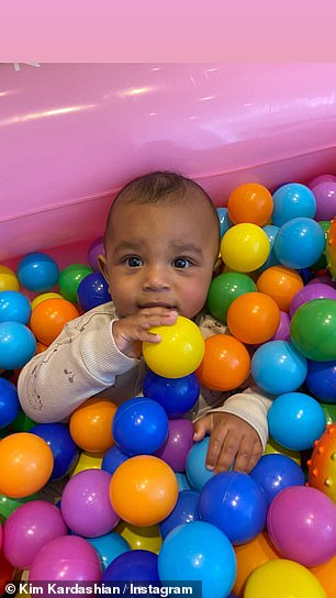 Having a ball: Kim's little boy seemed to sink deeper into the ball pit with each adorable photo