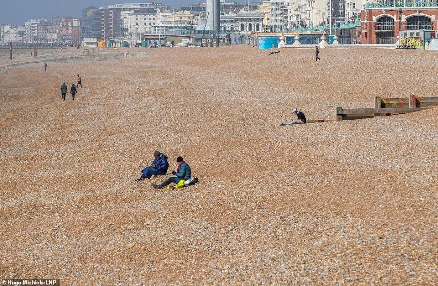 Un puñado de personas están esparcidas a lo largo de la playa, a pesar del pronóstico del clima cálido que continúa durante gran parte de esta semana.