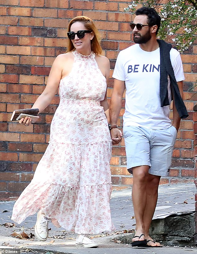 Pregnant Jules Robinson showed off her growing bump in a floral dress on Sunday morning with husband Cam Merchant as they were spotted emerging from their Sydney home for the first time since announcing their baby news hours earlier