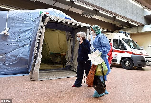 A total of 300 doctors were infected in a hospital in Lombardy - the area most affected by the virus - while 12,000 hospital staff were diagnosed across the country. In the photo: a doctor helps an elderly woman at the Molinette hospital in Turin