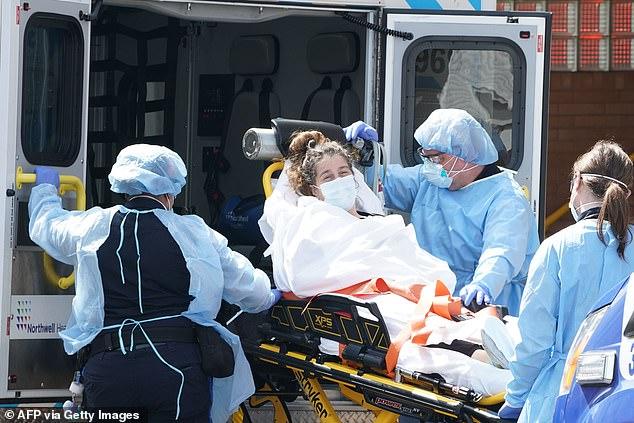 A woman arrives by ambulance at Wyckoff Hospital in Bushwick in Brooklyn, NYC, Sunday
