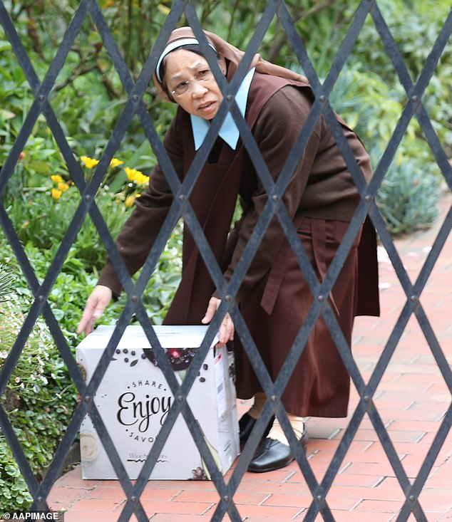 A nun picks up a case of wine placed on Tuesday outside a Kew monastery. Cardinal George Pell to be invited Tuesday evening