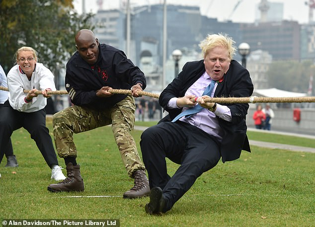 Mr Johnson joins in for a game of tug of war with members of the armed forces in 2015 at Potters Field in London