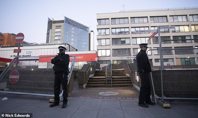 Police guard an entrance to St Thomas' Hospital in London, where Mr Johnson is being cared for, as sources said he is not on a ventilator but doctorss fear he could need one