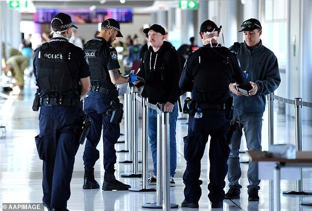 Australian Federal Police are pictured speaking to travelers arriving at Brisbane Airport on April 3. Only residents or those with a permit are allowed to enter the state while fighting COVID-19