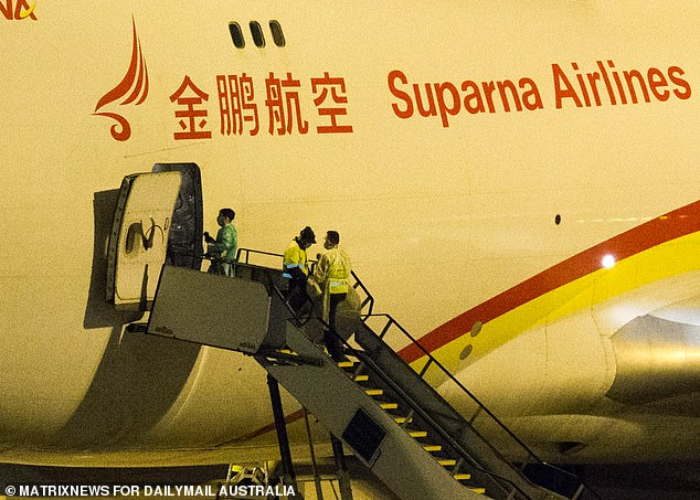 One man dressed in protective gear and another two in hi-vis workwear were spotted near the plane's entrance